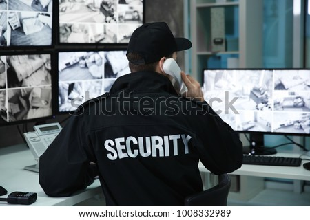 Male security guard talking by telephone in surveillance room Royalty-Free Stock Photo #1008332989