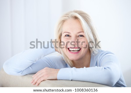 Active beautiful middle-aged woman smiling friendly and looking in camera in living room. Woman's face closeup. Realistic images without retouching with their own imperfections. Selective focus. #1008360136