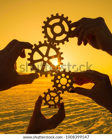 silhouettes four hands collect the gear from the gears of the puzzle pieces. against the background of sunlight. The concept of a business idea. Teamwork #1008399547