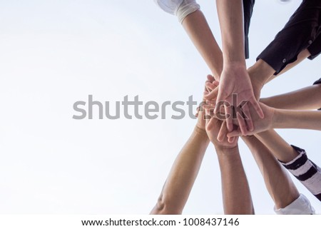 Teamwork group of young people putting their hands together for showing unity . #1008437146