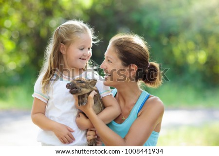 Kids play with farm animals. Child feeding domestic animal. Young mother and little girl holding wild boar baby at petting zoo. Kid playing with newborn pig. Children and pets. Family at farm vacation #1008441934