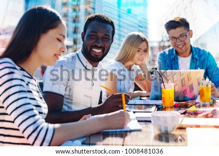 Working together. Handsome cheerful afro-american man smiling and holding a pencil while working with his colleagues on a project #1008481036