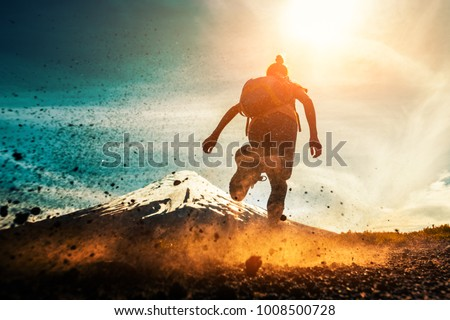 Woman athlete runs on a dirty and dusty ground with volcano on the background. Trail running athlete working out in the mountains #1008500728