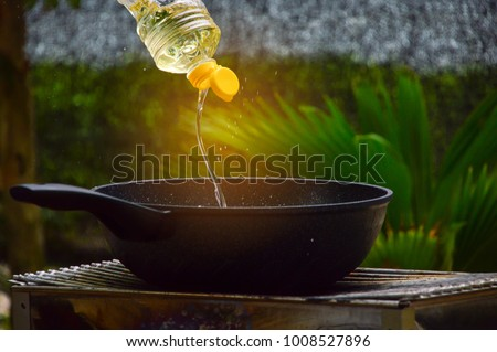 Pour the vegetable oil into the cooking pan. #1008527896