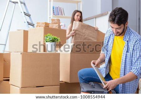 Young family unpacking at new house with boxes #1008554944