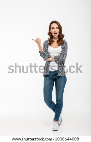 Full length portrait of a happy casual girl winking and pointing finger away isolated over white background Royalty-Free Stock Photo #1008644008