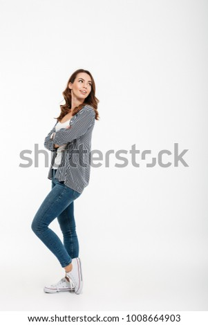 Full length portrait of a lovely casual girl standing and looking away isolated over white background #1008664903