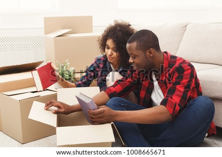Happy african-american couple unpacking moving boxes and taking out books in new apartment, copy space #1008665671