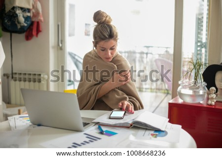 Young beautiful woman works on computer from a home with a laptop on a white desk as a freelancer.