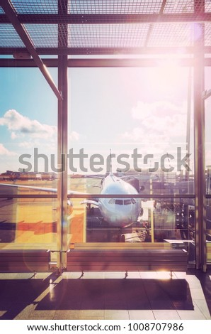 Departure hall at an airport at sunset, color toned travel and transportation concept picture with lens flare effect. #1008707986