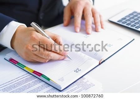 Business man in dark suit writing  in his datebook #100872760
