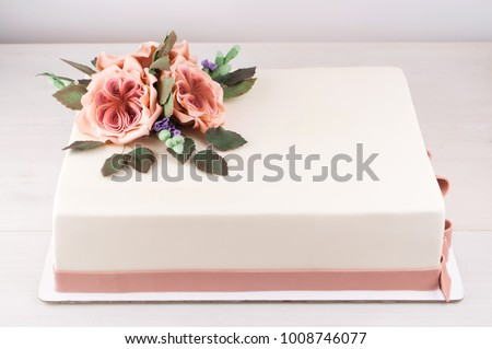 Rectangular art cake decorated with pink flowers and green leaves from mastic on a white wooden table. Picture for a menu or a confectionery catalog.
