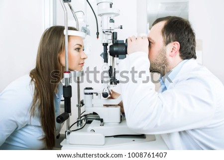 male doctor and a female patient, during a vision test, while in a medical clinic #1008761407