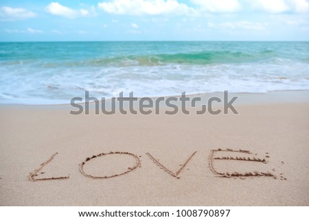 The hand writing word love on the beach by the sea with white waves and blue sky background #1008790897