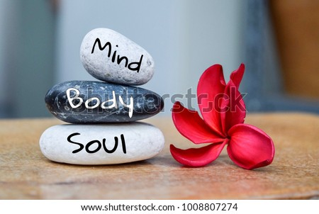Holistic health concept of zen stones with deep red plumeria flower on blurred background. Text body mind soul. Royalty-Free Stock Photo #1008807274