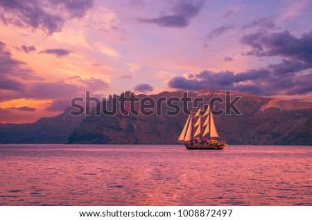 Sailboat in Santorini, Greece. Sailing ship navigate near an island in Cyclades. The photo is taken at sunset. #1008872497