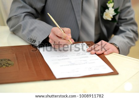 The groom puts his signature in the marriage document #1008911782