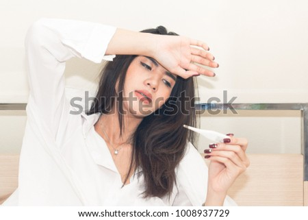 Woman measuring temperature her body on the bed. person got fever lying on the bed. Royalty-Free Stock Photo #1008937729