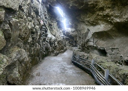 Mountain pass made by people, simple mountain tunnel with cables and lighting, walls are made of wild stone, quarry, layered stone, limestone. amera moves along stone passage #1008969946
