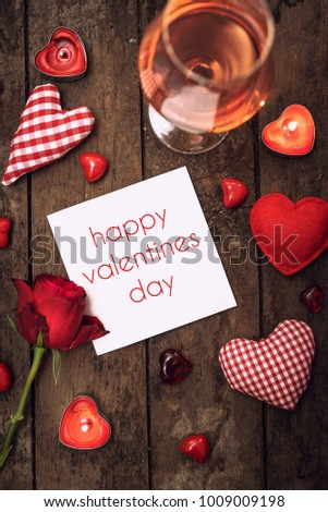 Preparations for Valentine's Day: a notebook for congratulation or sweet notes, gift, candy in the form of hearts, red ribbon and top view, copy space #1009009198
