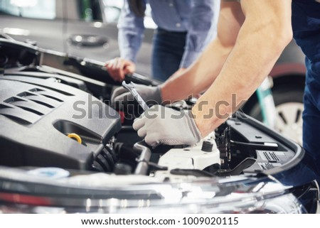 A man mechanic and woman customer look at the car hood and discuss repairs. #1009020115