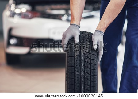 Mechanic holding a tire tire at the repair garage. replacement of winter and summer tires. #1009020145