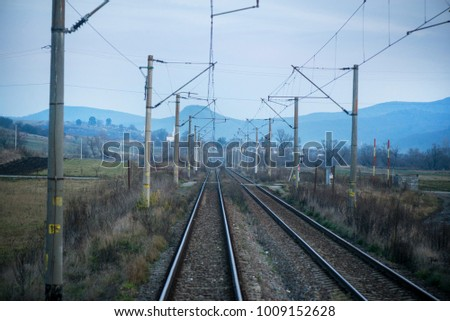 Eastern European railroad across Transilvania. Mountain landscape in the backgroun. Scary, dangerous scene in winter with naked trees and polluted nature #1009152628