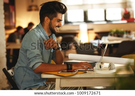 Casual startup programmer and designer working on new project .He sitting at the company cafe and using using laptop.Positive emotions. #1009172671