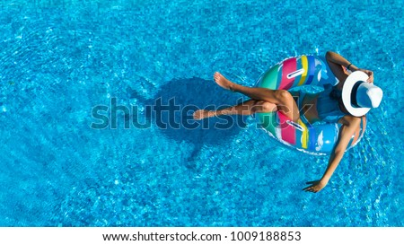 Aerial top view of beautiful girl in swimming pool from above, relax swim on inflatable ring donut and has fun in water on family vacation, tropical holiday resort  Royalty-Free Stock Photo #1009188853