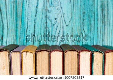Stacks of colored books on a wooden table. concept of reading habits #1009203517