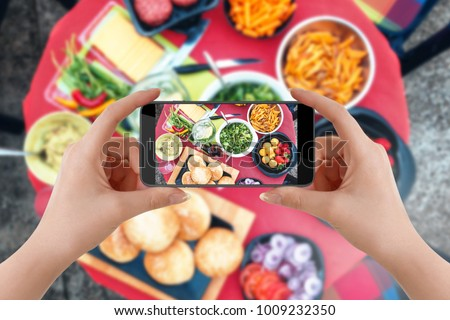 Girl taking picture of vegetarian food on table with her smartphone