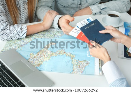 Young couple in a tour agency communication with a travel agent travelling concept passports and tickets #1009266292