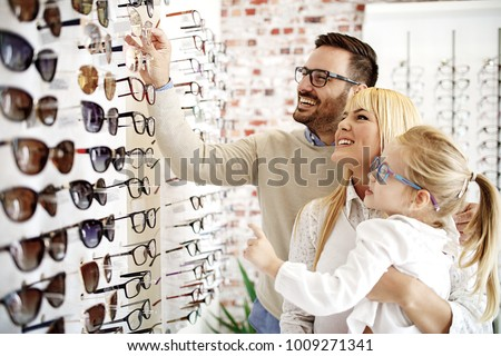 Four year little girl in optics store choosing glasses with her father. Ophtamologist helping.  #1009271341