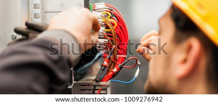 Electrician engineer tests electrical installations and wires on relay protection system. Bay control unit. Medium voltage switchgear #1009276942
