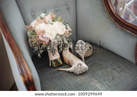 Brides wedding shoes with a bouquet with roses and other flowers on tha arm chair #1009299649