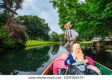Christchurch, New Zealand - December 14th ,2017 :  Young girl wearing hijab  punt on the Avon River, passing through Hagley Park, in Christchurch, New Zealand. #1009306519