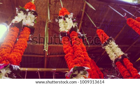 Bunch of marigold garland with white lily hanging for sale low angle shot from india.  #1009313614