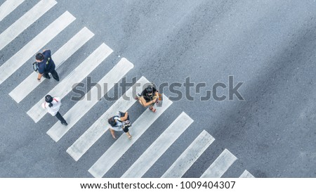 From the top view of people walk on street pedestrian crossroad in the city street with the motorcycle drives pass road ,bird eye view. #1009404307