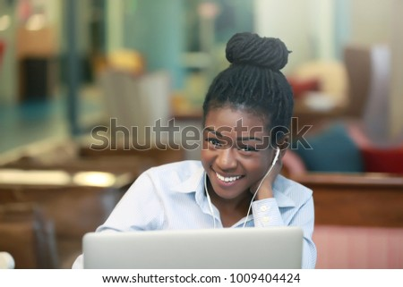 Lovely African-american female looking at camera and smiling while listening to music near laptop  #1009404424