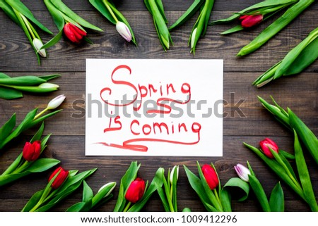 Spring is coming lettering surrounded by colorful tulips on dark wooden background top view #1009412296