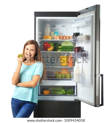 Woman with apple near full refrigerator on white background #1009434058