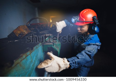 Young miner man underground in mine for coal mining in overalls is busy with work, repairing against backdrop of equipment. Portrait. #1009456330