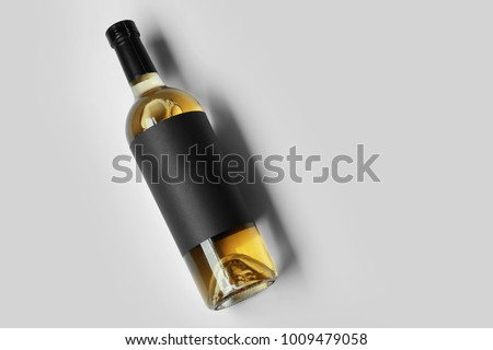 Bottle of wine with blank label on light background. Mock up for design #1009479058