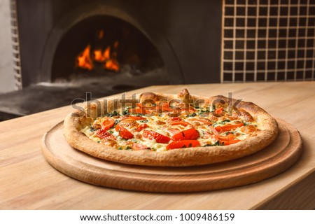 Tasty pizza on table against stove in kitchen #1009486159