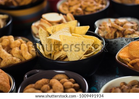 Salty snack including peanuts, potato chips and pretzels served as party food in bowls Royalty-Free Stock Photo #1009491934