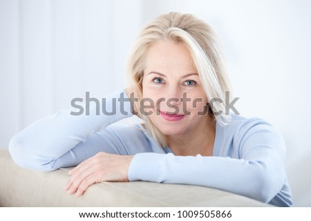 Active beautiful middle-aged woman smiling friendly and looking in camera in living room. Woman's face closeup. Realistic images without retouching with their own imperfections. Selective focus. #1009505866