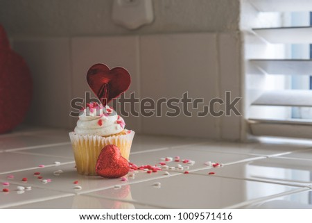 Single cupcake with heart tooth pic and small heart in front and text space on the right
