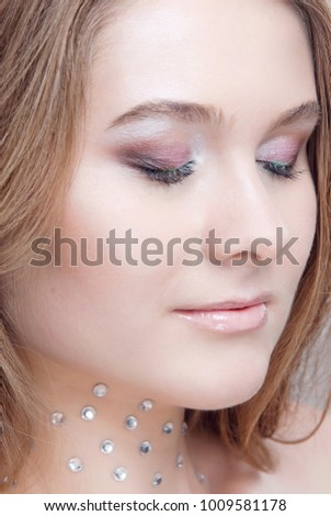 Glamorous makeup for the eyes closed blonde with pure skin and rhinestones on the neck close-up #1009581178