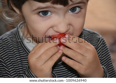 the child eats strawberries  #1009626940