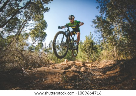 Wide angle view of a mountain biker speeding downhill on a mountain bike track in the woods Royalty-Free Stock Photo #1009664716